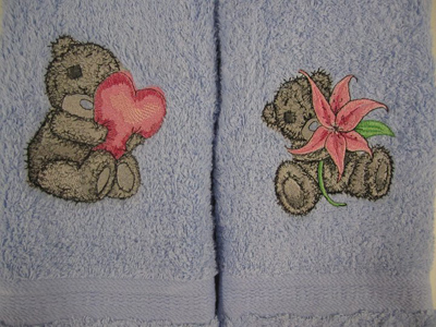 two towels embroidered with teddy bear designs